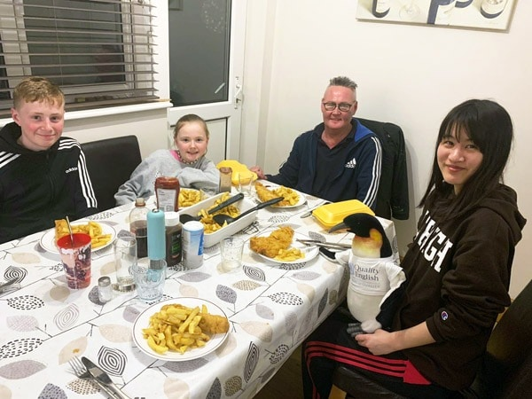 Quentin the penguin has fish and chips at his host family's house